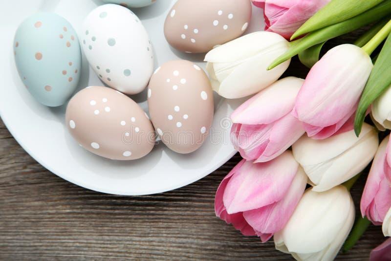 Tulipanes con los huevos de Pascua en placa foto de archivo