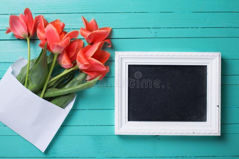 Tulipanes coralinos frescos en el sobre blanco y la pizarra vacía para el te foto de archivo