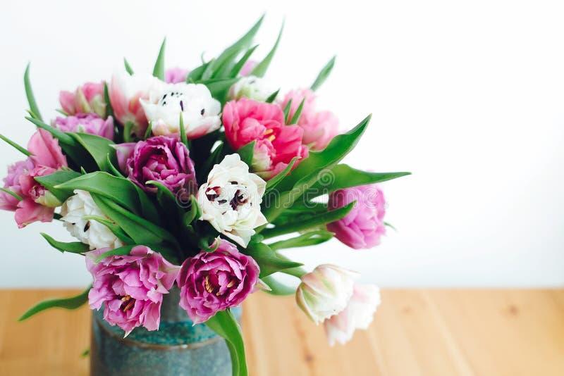 Tulipanes dobles hermosos de la peonía en luz Rosa colorido y ramo púrpura de los tulipanes en florero en la tabla con el espacio fotos de archivo