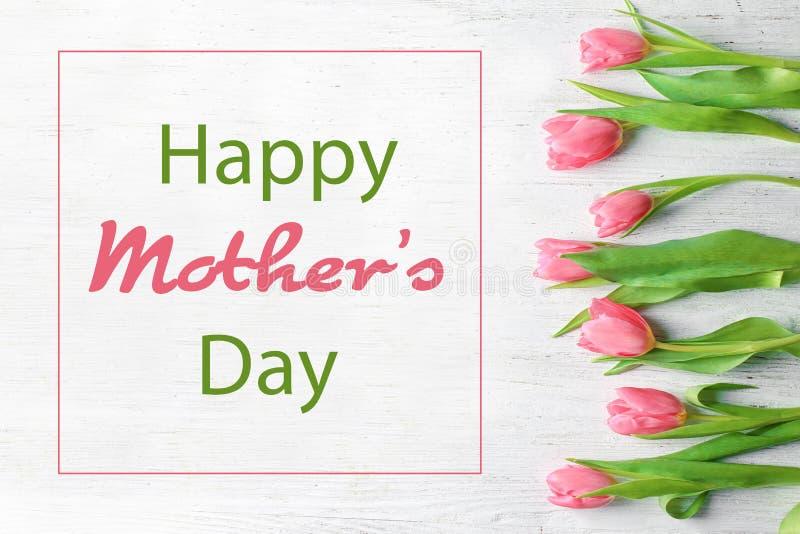 Tulipanes hermosos y saludo del día de madre feliz en el fondo de madera blanco, visión superior imagen de archivo