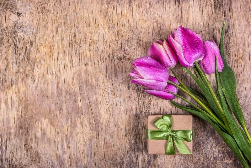 Tulipanes p?rpuras frescos Caja y tulipanes de regalo Caja de regalo con la cinta Copie el espacio fotos de archivo