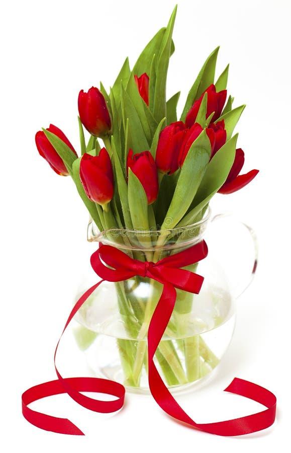 Tulipanes rojos en un florero con una cinta roja fotos de archivo