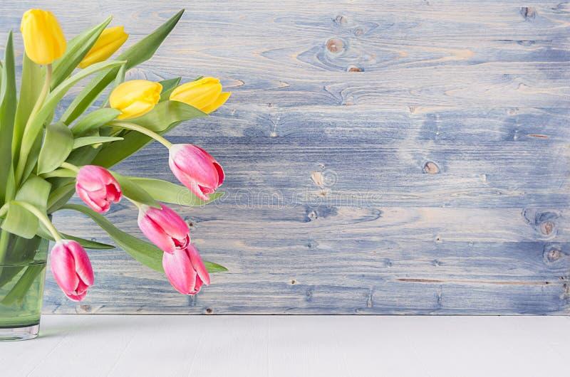 Tulipanes rojos y amarillos del medio ramo en florero del vidrio verde en fondo de madera lamentable azul con el espacio de la co fotos de archivo