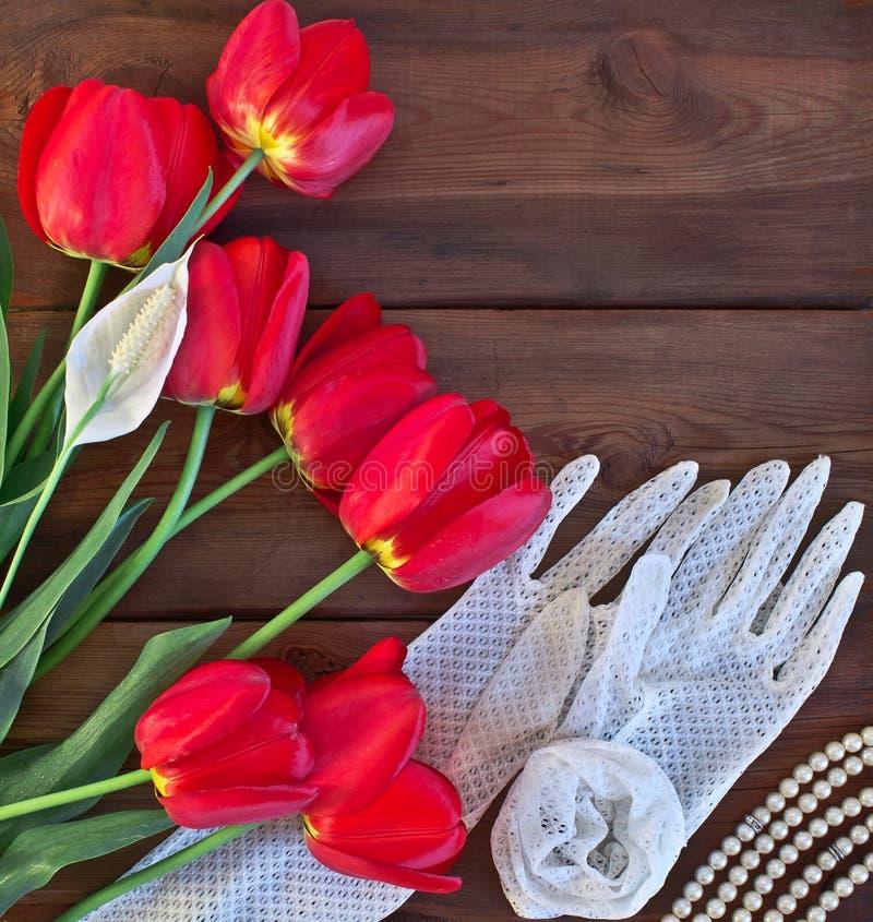 Tulipanes rojos y guantes blancos del cordón imagen de archivo