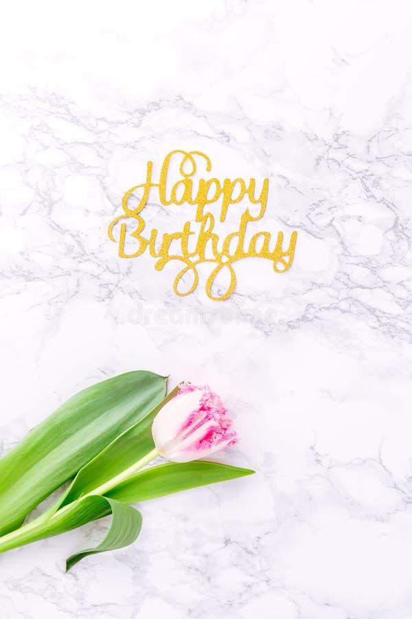 Tulipanes rosados y letras del feliz cumpleaños del oro en la parte posterior blanca del mármol imagen de archivo