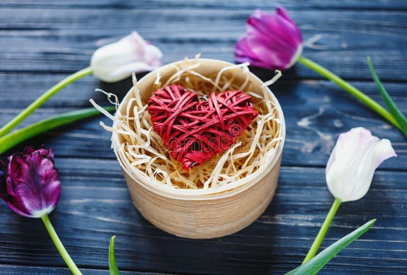Tulipanes violetas rosados hermosos coloridos y corazón rojo en caja de madera redonda en la tabla de madera gris Tarjetas del dí foto de archivo