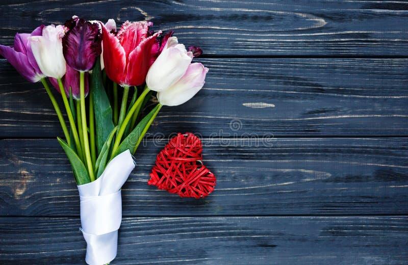 Tulipanes violetas rosados hermosos coloridos y corazón rojo en la tabla de madera gris Tarjetas del día de San Valentín, fondo d fotos de archivo libres de regalías