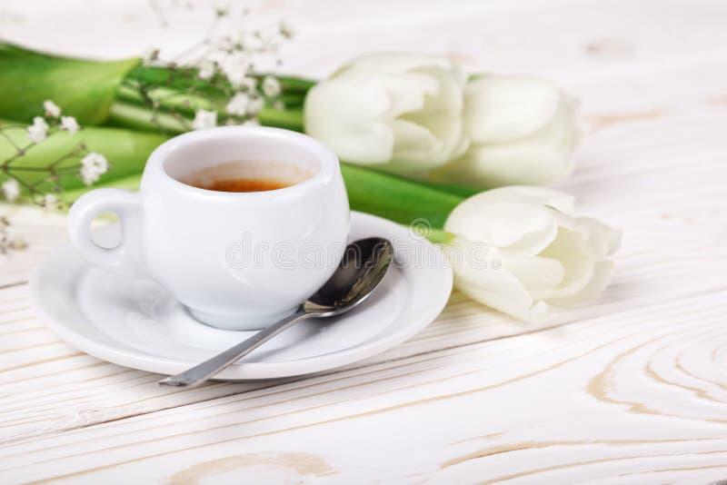 Tulipanes y café de la primavera en un primer de madera blanco del fondo Fondo del día de madre, el día de las mujeres, cumpleaño foto de archivo