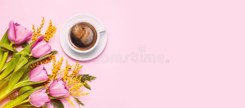 Tulipanes y flores rosados de la mimosa con la taza de café en fondo rosado foto de archivo