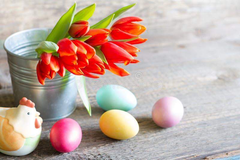 Tulipanes y huevos rojos de la primavera de Pascua en fondo de madera con la gallina imágenes de archivo libres de regalías