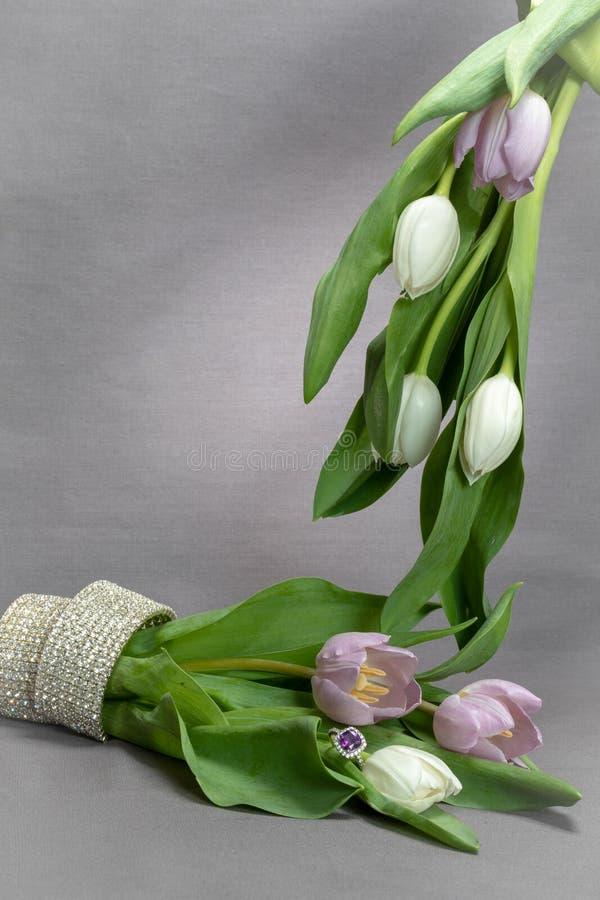 Tulipanes y joyería púrpuras en fondo gris imagen de archivo