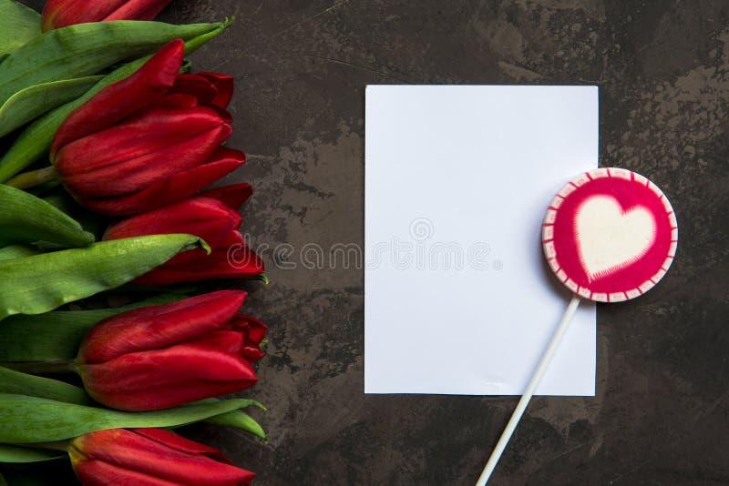 Tulipanes y piruleta rojos con el espacio de la copia para su texto imagen de archivo