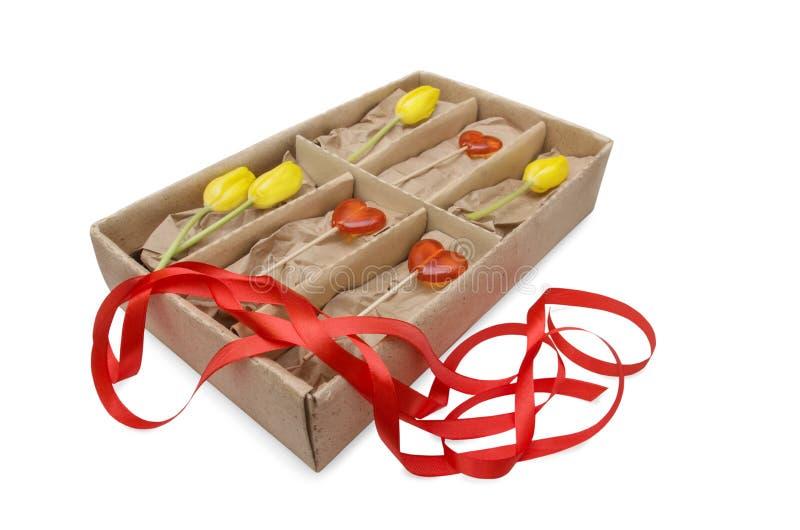 Tulipanes y piruletas rojas del corazón en una caja con un arco Día del ` s de la tarjeta del día de San Valentín y concepto del  imágenes de archivo libres de regalías