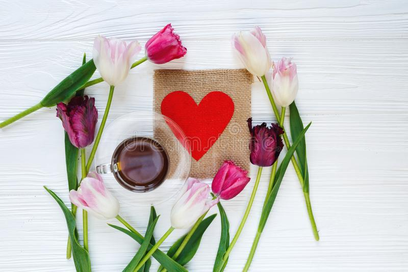 Tulipanes y taza de café hermosos coloridos en el centro en la tabla de madera blanca Tarjetas del día de San Valentín, fondo de  foto de archivo libre de regalías