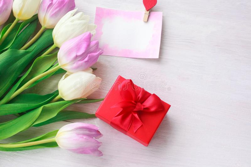 Tulipani bianchi e porpora e un regalo in una scatola rossa su un fondo di legno bianco Sorgente Giorno internazionale del ` s de fotografia stock libera da diritti