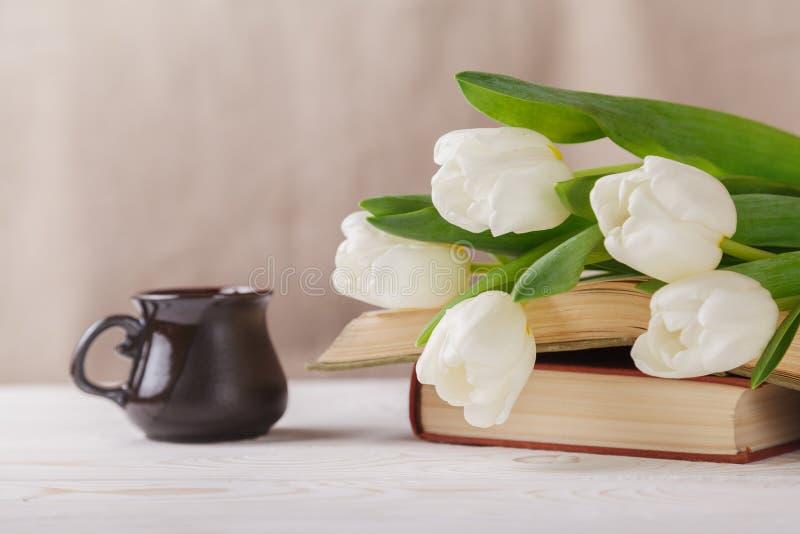 Tulipani bianchi, vecchi libri, una tazza di caffè nella distanza su un fondo beige Mattina, molla, lettura, pausa caffè fotografia stock libera da diritti