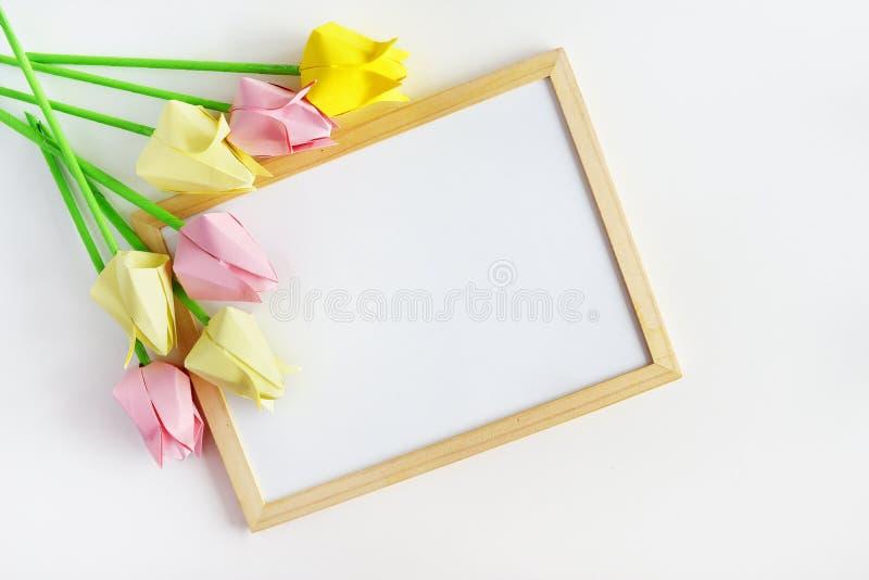 Tulipani degli origami su un fondo bianco, una struttura di legno immagine stock