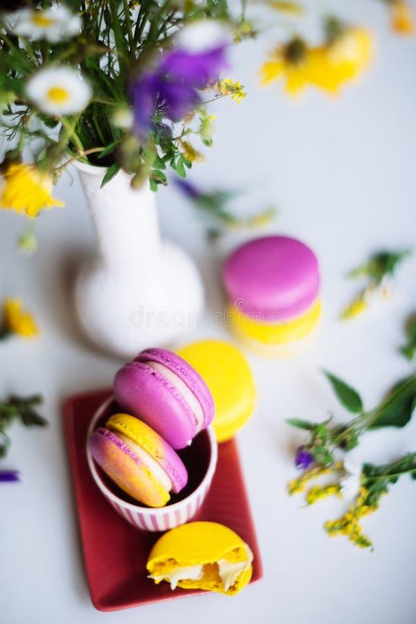Tulipani dei fiori di rosa e dei maccheroni sulla tavola di legno rustica bianca con il posto per testo Presenti il giorno di mad fotografia stock