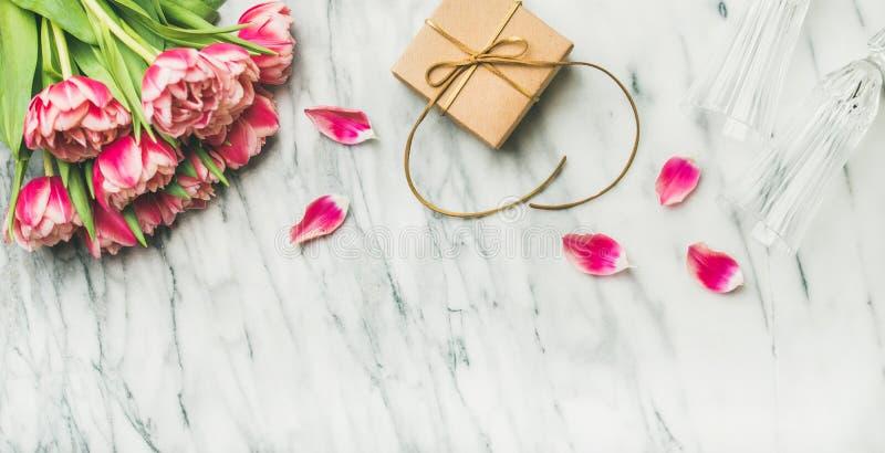 Tulipani, vetri del champagne e contenitore di regalo rosa con lo spazio della copia fotografia stock