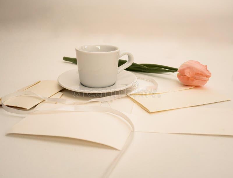 Tulipano rosa su una tavola con le lettere, le buste e la tazza di caffè fotografie stock