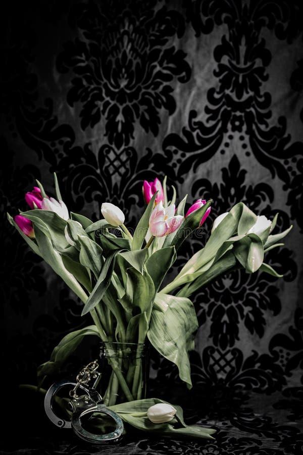 Tulipany w wazie z kajdankami fotografia stock
