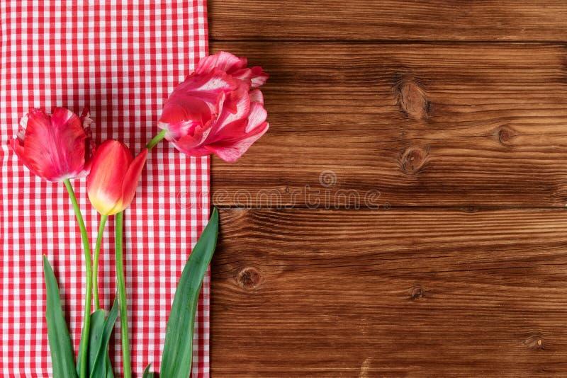 Tulipany z czerwonym w kratkę tablecloth na kraju drewnianym tle Odgórny widok, tekst przestrzeń zdjęcie stock
