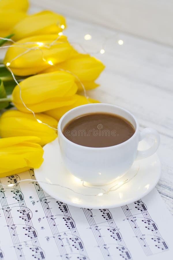 Tulipas amarelas com festões, uma xícara de café, cappuccino e notas em um de madeira branco foto de stock royalty free