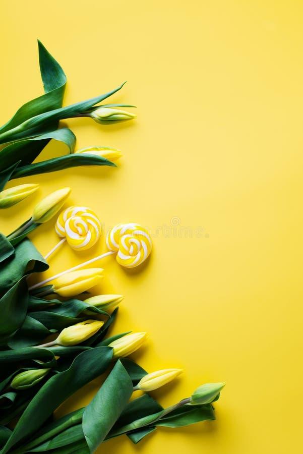 Tulipas amarelas com os doces do pirulito sobre o fundo amarelo, beira fotografia de stock royalty free
