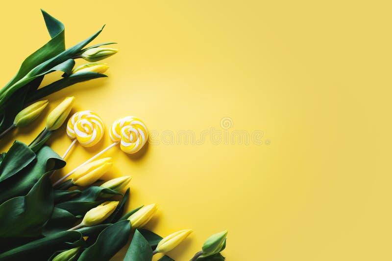 Tulipas amarelas com os doces do pirulito sobre o fundo amarelo, beira imagem de stock