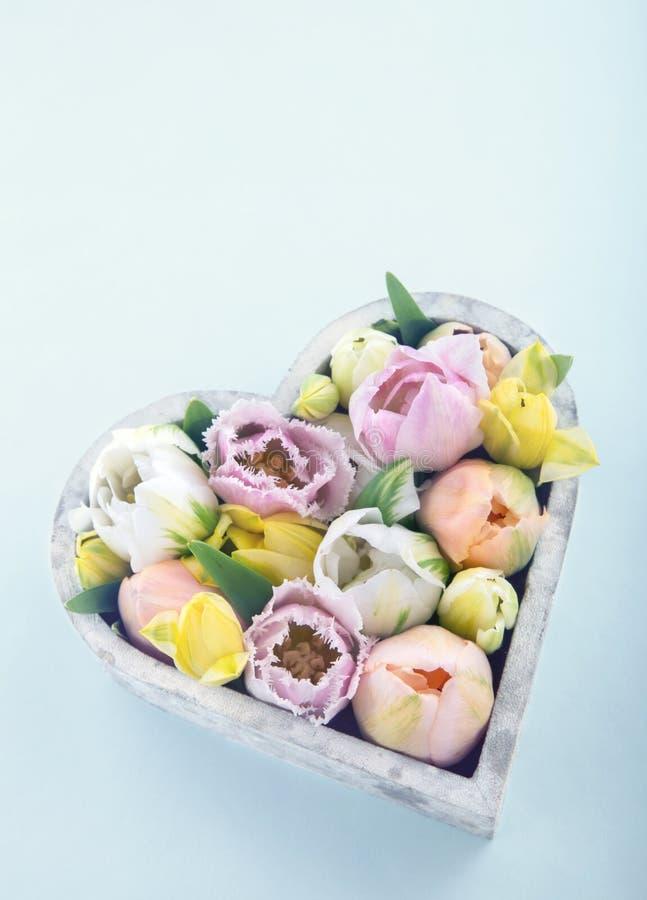 Tulipas coloridas em um vaso dado forma coração foto de stock