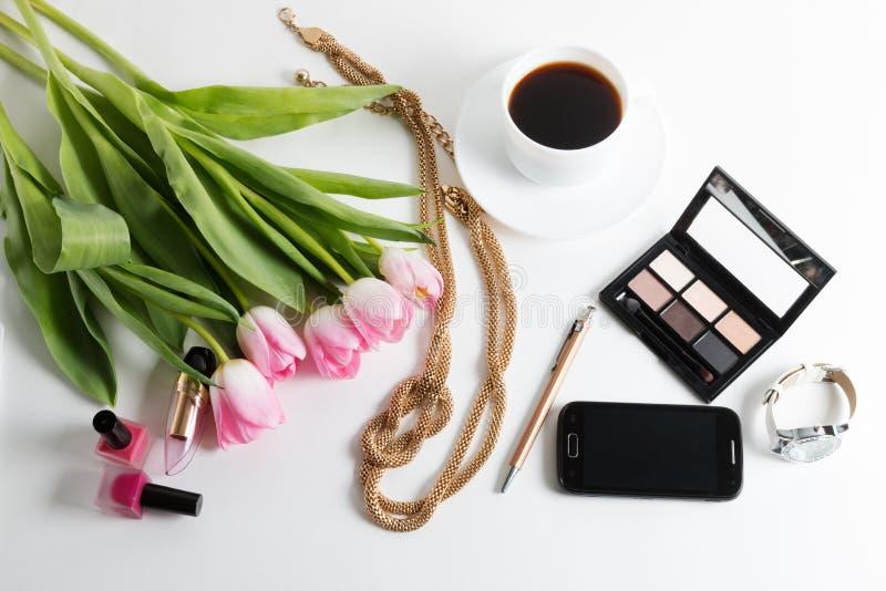 Tulipas cor-de-rosa, bijouterie, cosméticos, pena, relógio de pulso, café foto de stock