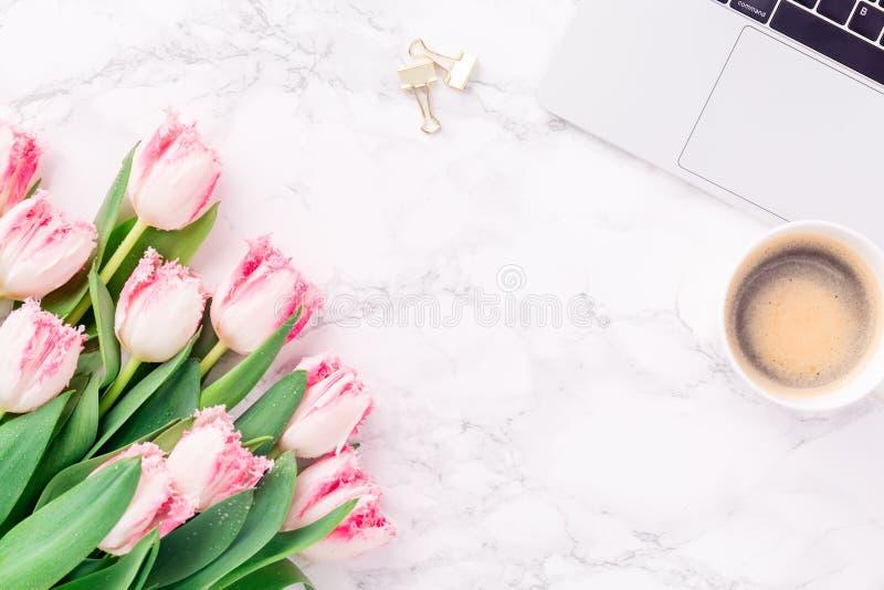 Tulipas cor-de-rosa com estacionário festivo e café no mármore branco b fotografia de stock royalty free