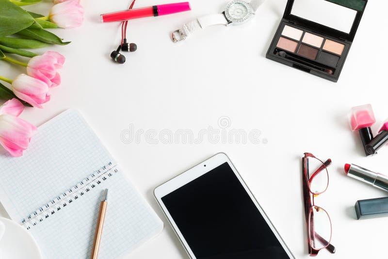 Tulipas cor-de-rosa, tabuleta, cosméticos, relógio de pulso, bloco de notas imagem de stock