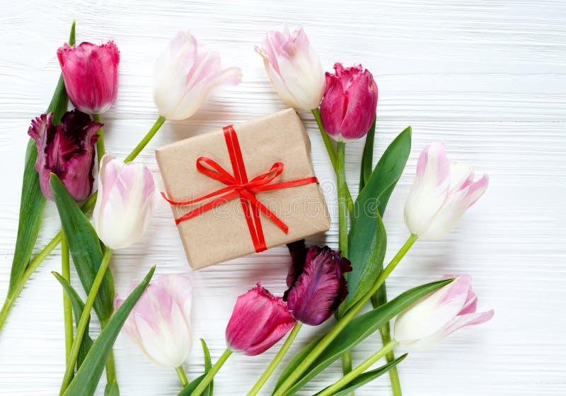 Tulipas e caixa de presente bonitas coloridas na tabela de madeira branca Valentim, fundo da mola zombaria floral acima com copys foto de stock royalty free