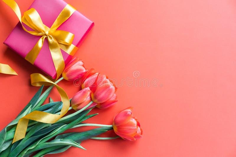 Tulipas e caixa de presente bonitas no fundo alaranjado Conceito dos feriados Copie o espa?o fotografia de stock royalty free