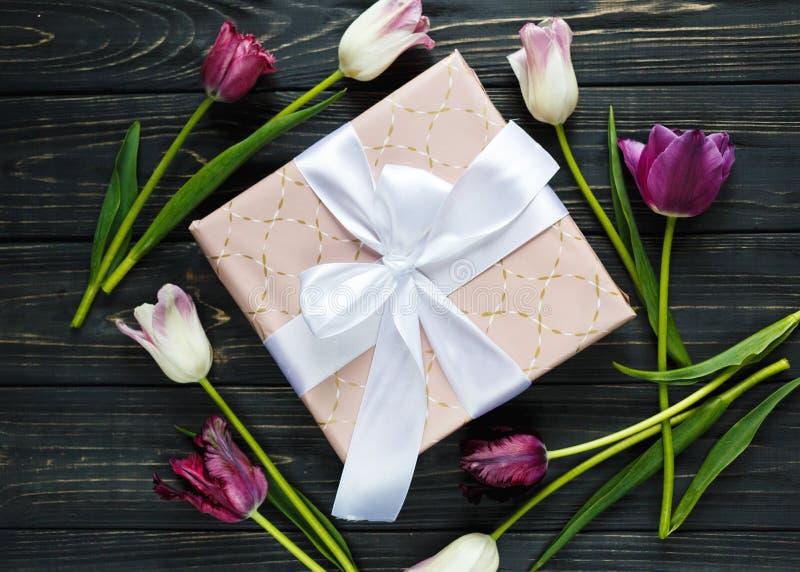 Tulipas e caixa de presente violetas cor-de-rosa bonitas coloridas na tabela de madeira cinzenta Valentim, fundo da mola fotos de stock royalty free