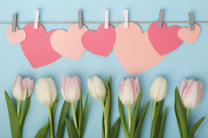 Tulipas e corações de papel cor-de-rosa como a decoração do dia de mãe fotografia de stock