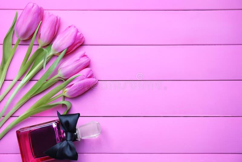 Tulipas e garrafa bonitas do perfume no fundo de madeira da cor foto de stock royalty free