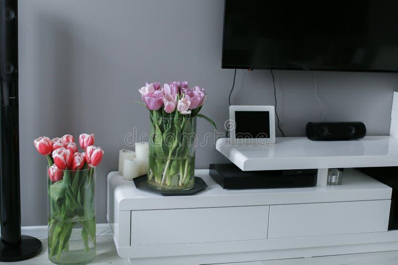 Tulipas em um vaso em uma tabela de madeira Interior escandinavo Modelo imagem de stock