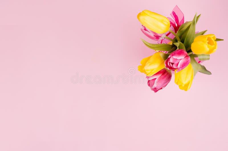 Tulipas frescas da mola amarelas e ramalhete vermelho no fundo do rosa pastel imagem de stock
