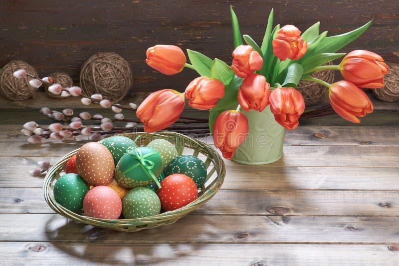 Tulipas, ovos da páscoa e decorações vermelhos da primavera no wo rústico imagem de stock