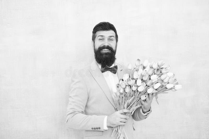 Tulipas para o querido Ramalhete bem preparado das flores da posse do la?o do smoking do desgaste do homem Convide-a que data Hom foto de stock