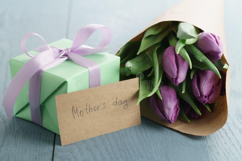 Tulipas roxas no papel do ofício com o cartão do dia da caixa de presente e de mães no fundo de madeira azul fotografia de stock
