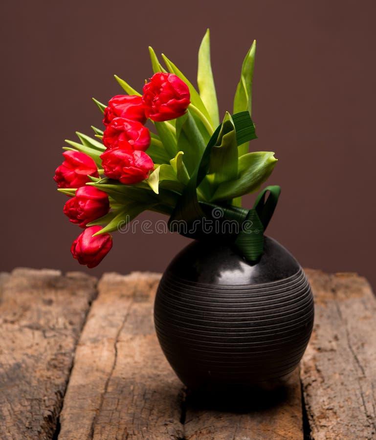 Tulipas vermelhas bonitas no vaso preto foto de stock royalty free