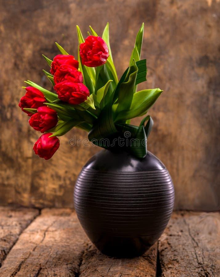Tulipas vermelhas bonitas no vaso preto fotografia de stock royalty free