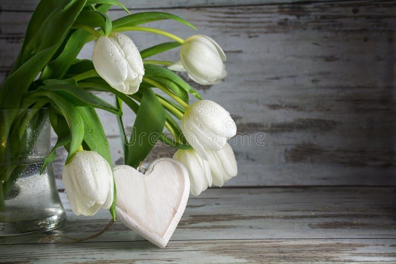 Tulipes blanches et une forme de coeur de bois contre un vintage en bois image libre de droits