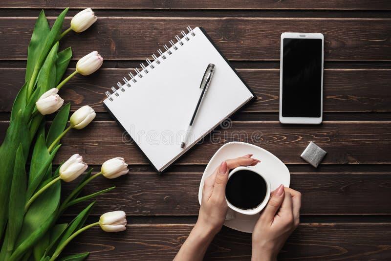 Tulipes blanches sur une table en bois avec un carnet et un smartphone vide et une tasse de café chez les mains des femmes image stock