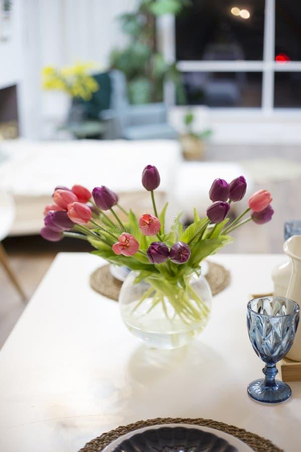 Tulipes dans un support de vase sur une table de cuisine blanche à la salle photo libre de droits