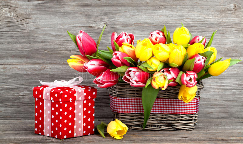 Tulipes de ressort dans le panier en bois, boîte-cadeau à pois rouge photographie stock