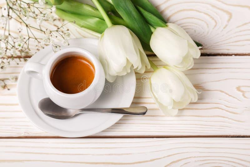 Tulipes de ressort et café sur un fond en bois blanc, vue supérieure Fond du jour de mère, le jour des femmes, anniversaire de ma photo libre de droits